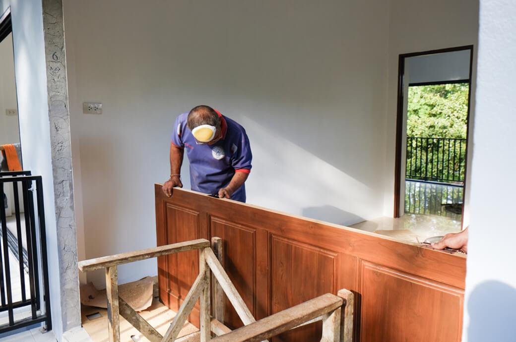 Плотник устанавливает шпонированную дверь